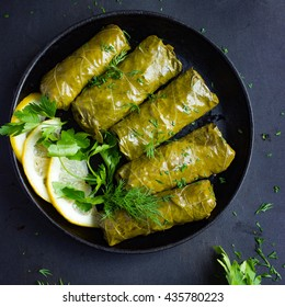 Dolma, stuffed grape leaves with rice and meat. Top view. Black background. square image