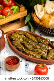 Dolma (tolma, sarma) - stuffed grape leaves with rice and meat. On kitchen table with yogurt, bread, vegetables. Traditional Caucasian, Ottoman, Turkish and Greek cuisine - Image