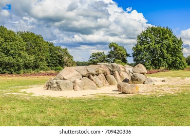 A dolmen, D53,  in the province of Drenthe in the Netherlands with a background of oak trees and a beautiful Dutch cloudy sky. A dolmen is construction work from the new stone age