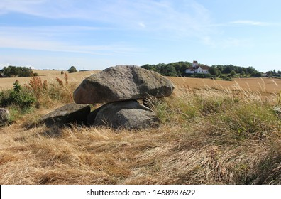 Dolmen at Kong Humbles Grave and Humble Church in the background wit surrounding rural scene. Langeland, Denmark.