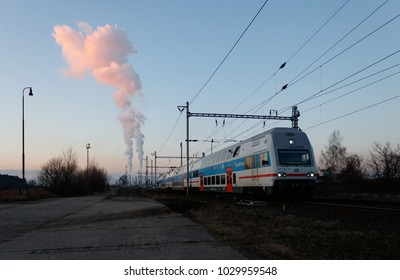Dolni Berkovice, Czech Republic / February 13, 2018 - Suburban commuter train City Elefant no. 971 020-3 going on track. Evening, sunset light coloring white smoke from factory chimneys in backgound.