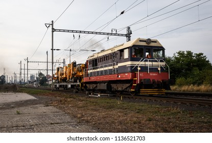 Dolni Berkovice, Czech Republic - July 17, 2018 - Blue and cream white diesel locomotive no. 721 035-4 transporting one car with yellow railway (railroad) building machine (appliance) by Skanska.