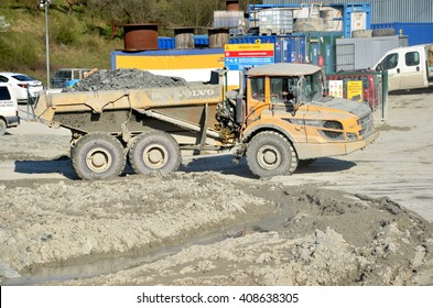 "Dolny Hricov, Slovakia - April 13, 2016: Dirty heavy Volvo dumper loaded by rock moving in work site. There is slovak highway labeled ""D1"" under construction."