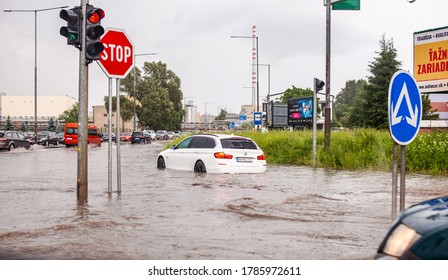Dolny Kubin, Slovak Republic - July 16, 2019: Luxury white car flooded during a rainstorm at an intersection.