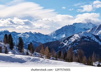 Dolomite mountains covered in snow at daylight. Blue sky with clouds. Belluno, Italy