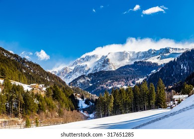 Dolomite mountains covered with white snow and green conifers in Italy