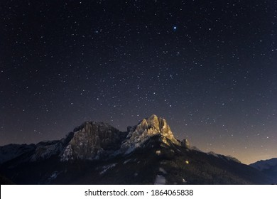 Dolomites by nightSky with stars on a winter night in val di fassa. Dolomites, forest and night lights of Pozza di Fassa