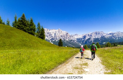 Dolomites. Family of hikers walking on a mountain path in summer time.