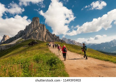 Dolomites, Italy, 19.7.2018: beautiful view of the Dolomites with hikers on path and grass in the foreground and hut, mountains and blue sky with clouds in the background taken on a sunny summer day