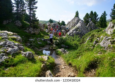 DOLOMITES, ITALY - AUG 6, 2018 - Hikers on a mountain trail in the Dolomites Alps, Italy