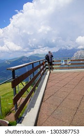 DOLOMITES, ITALY - AUG 6, 2018 - Hiker photographs the alpine view from terrace of a mountain hut in te Dolomites Alps, Italy