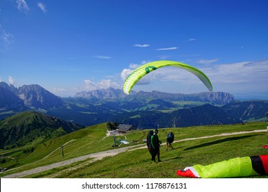 DOLOMITES, ITALY - AUG 7, 2018 - Parapentes launch from a high alpine meadow in the Dolomites Alps, Italy