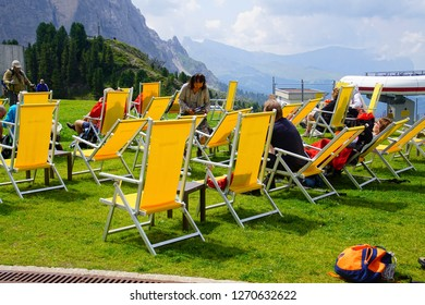 DOLOMITES, ITALY - AUG 7, 2018 - Hikers relax in yellow chairs in the Dolomites Alps, Italy