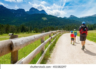 Dolomites Italy, family walking along a mountain path in a sunny