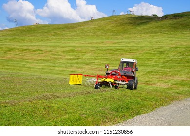 DOLOMITES, ITALY - JUL 24, 2018 - Raking hay in the summer alm meadow in the Dolomites Alps, Italy