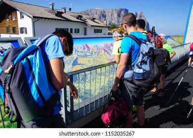 DOLOMITES, ITALY - JUL 24, 2018 - Hikers check the map before beginning their walk in the Dolomites Alps, Italy
