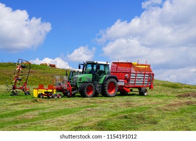 DOLOMITES, ITALY - JUL 24, 2018 - Tractor for making hay in the summer alm meadow in the Dolomites Alps, Italy