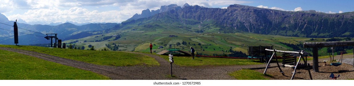 DOLOMITES, ITALY - JUL 24, 2018 - Panorama as hikers begin their walk in the Schlern area of Seiser Alm in the Dolomites Alps, Italy