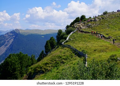 DOLOMITES, ITALY - JUL 24, 2018 - Hikers walking through high meadows of the Dolomites Alps, Italy