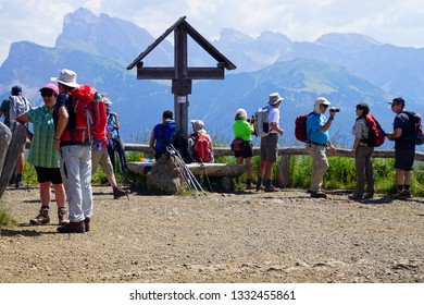 DOLOMITES, ITALY - JUL 24, 2018 - Hikers take a rest at small shrine in nthe Dolomites Alps, Italy