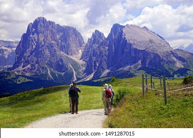 DOLOMITES, ITALY - JUL 24, 2018 - Hikers walking towards the Langkofel - Sasso Lungo and the Platkofel - Sasso Piato in the Dolomites Alps, Italy