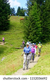 DOLOMITES, ITALY - JUL 25, 2018 - Hikers on a trail through a meadow of the Seiser Alm of the Dolomites Alps, Italy