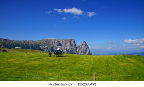 DOLOMITES, ITALY - JUL 25, 2018 - Helicopter landing in the Seiser Alm after military parapente exercises in the Dolomites Alps, Italy