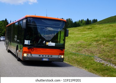 DOLOMITES, ITALY - JUL 25, 2018 - Local bus on small  road through meadows of Seiser Alm, Dolomites Alps, Italy
