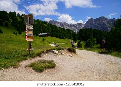 DOLOMITES, ITALY - JUL 25, 2018 - Sign post for trails on a meadow of the Dolomites Alps, Italy