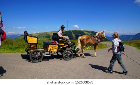 DOLOMITES, ITALY - JUL 25, 2018 - Horse and carriage and hiker on a trail through a meadow of the Seiser Alm of the Dolomites Alps, Italy