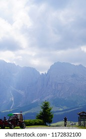 DOLOMITES, ITALY - JUL 27, 2018 - Bicyclist and Langkofel massif viewed from alpine meadows of the Dolomites Alps, Italy