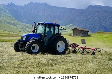 DOLOMITES, ITALY - JUL 27, 2018 - Blue tractor raking hay in meadow of the Dolomites Alps, Italy