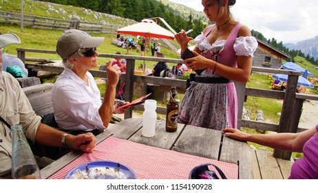 DOLOMITES, ITALY - JUL 29, 2018 - Waitress takes lunch order at alpine hut Berghause Platzwiese - Albergo  Prato Piazza, Dolomites Alps, Italy