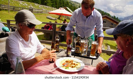 DOLOMITES, ITALY - JUL 29, 2018 - Waiter delivers drinks at alpine hut Berghause Platzwiese - Albergo  Prato Piazza, Dolomites Alps, Italy