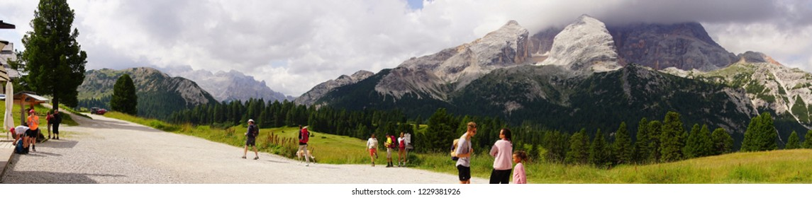 DOLOMITES, ITALY - JUL 29, 2018 - Hikers on a trail through an alpine meadow in the Schlern area of the  Dolomites Alps, Italy