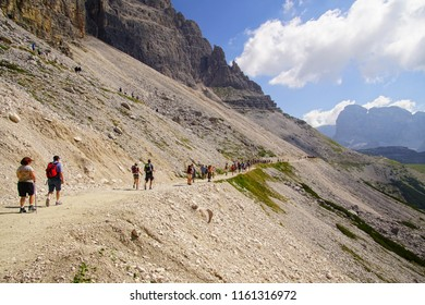 DOLOMITES, ITALY - JUL 31, 2018 - Large group of hikers moves across scree slope to an alpine hut in the Drei Zinnen area of the  Dolomites Alps, Italy