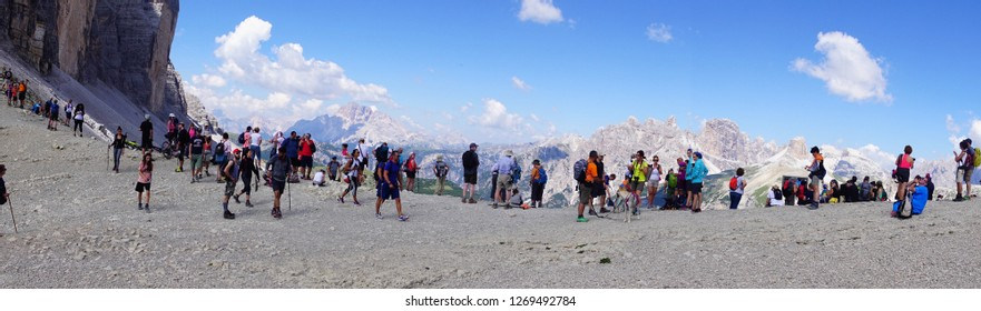 DOLOMITES, ITALY - JUL 31, 2018 - Large group of hikers on the pass saddle under the Drei Zinnen area of the  Dolomites Alps, Italy