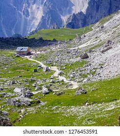 DOLOMITES, ITALY - JUL 31, 2018 - Hikers pass aan alpine hut on the way to the  Drei Zinnen area of the  Dolomites Alps, Italy