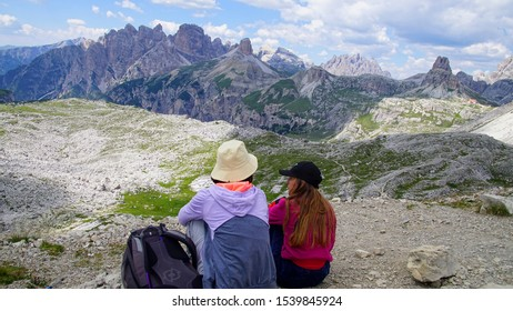 DOLOMITES, ITALY - JUL 31, 2018 - Young women enjoy the view near the Drei Zinnen hut set among the peaks of the Dolomites Alps, Italy