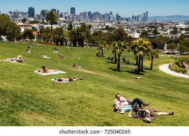 Dolores Park, San Francisco, California, USA. People laying on grass in Dolores Park with San Francisco skyline in background. Landscape orientation. Photo taken on July 11, 2016.
