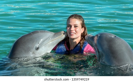 Dolphins kiss young woman in blue water. Smiling woman swimming with dolphin. Blue ocean water background.