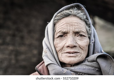 Dolpo, Nepal - circa May 2012: Old woman with wrinkles on her face and brown eyes wears grey headcloth in Dolpo, Nepal. Documentary editorial.
