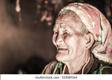 Dolpo, Nepal - circa May 2012: Old smiling woman with short grey hair and colourful headcloth wears brown shirt looks to left in Dolpo, Nepal. Documentary editorial.