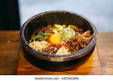 Dolsot bibimbap - Korean mixed rice, Include steamed rice, vegetables, pork and fried egg on top, served in a hot stone pot, Dolsot means stone pot in Korean.