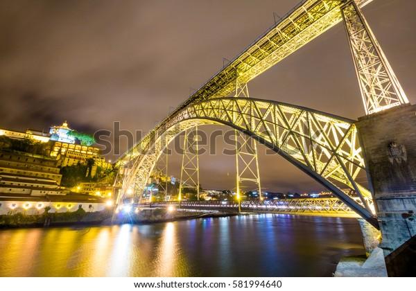 Dom Luis bridge over Douro river at night in Porto Portugal