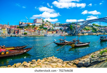 Dom Luis I bridge and traditional boats on Rio Douro river in Porto, Portugal