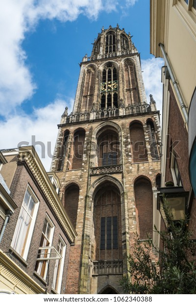 Dom tower in Utrecht seen from below against a clear blue sky with some clouds.
