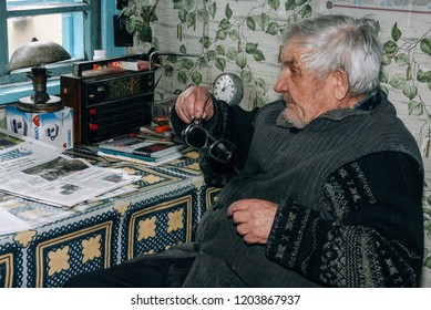 DOMASHOVE, Volyn / UKRAINE - March 24 2009: Senior man sitting waiting with a clock in a country house