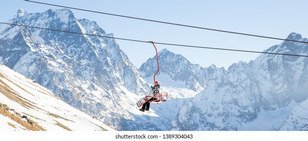 DOMBAI, RUSSIA - JANUARY 3, 2014: People are lifting on open lft high up in Caucasus mountains