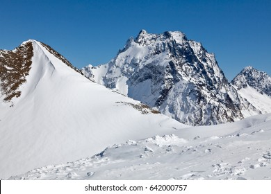 Dombai in the spring. A view of the tops of the Caucasian ridge and Mount Dombai-Ulgen (4046 m)